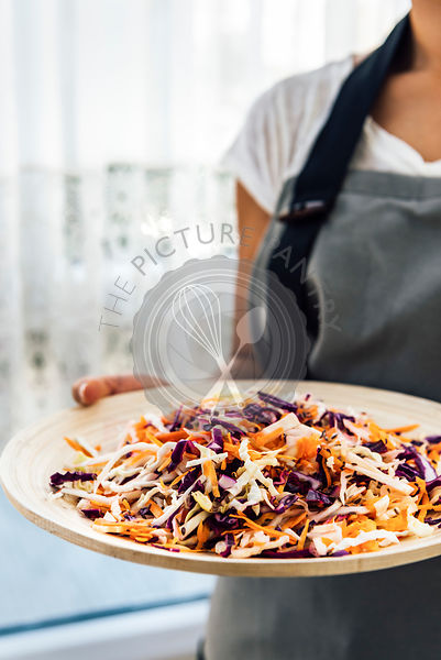 A woman with a white T-shirt and a grey apron holding a wooden bowl with coleslaw made with shredded carrot, white and purple cabbage photographed from front view.