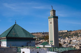 The medina roofline from the upper story of a carpet shop with Mosque and minarete in foreground, Fes, Morocco; Landscape