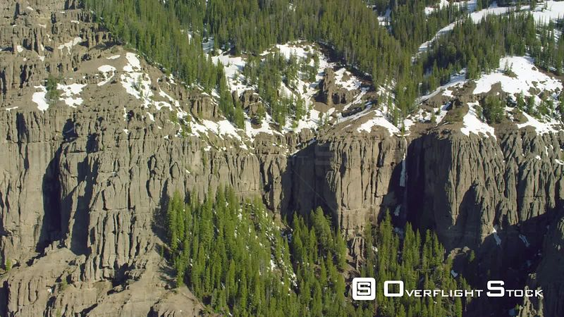 A tall waterfall cascades down steep cliffs within the southern flank of the Absaroka mountain  Range in Yellowstone National Park