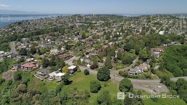 Aerial perspective flying over city houses on sunny day in Pacific Northwest