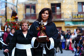 A female member of the brotherhood of Señor de las Caidas / The Fallen Christ carries a small statue during Good Friday procession, Plaza Murillo, La Paz, Bolivia