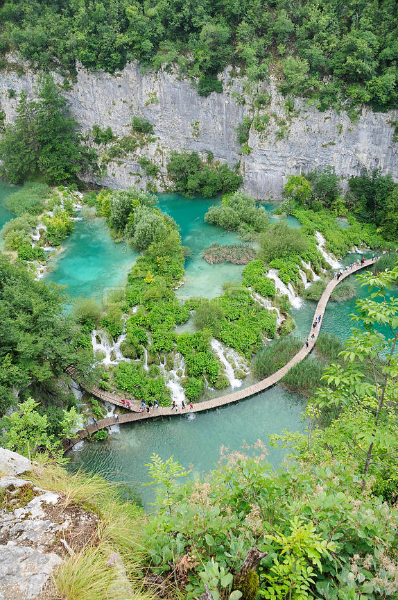 Overview of tourists walking on boardwalk below Velike kaskade waterfalls, with limestone cliffs in the background, Plitvice Lakes National Park, Croatia, July 2010.