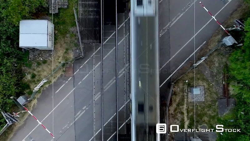 Vertical aerial view of railway level crossing and train, filmed by drone in summer, United Kingdom