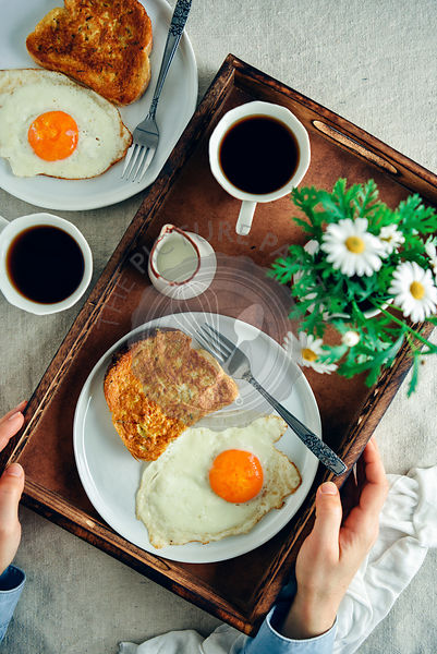 A woman holding a wooden tray with an easy French toast served with a fried egg on the side on a white plate, a cup of coffee, milk and spring flowers photographed from top view. Another plate with a french toast and an egg and another coffee cup accompany.