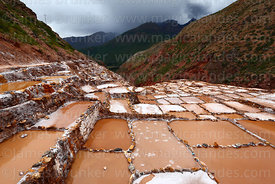 View over salt evaporation ponds and terraces at Las Salineras to Urubamba Valley, Maras, near Cusco, Peru