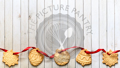 Border of Christmas shaped cookies threaded on red ribbon along a wooden background.