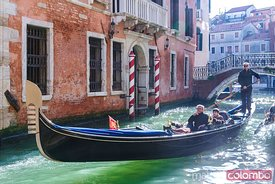 Gondola with adult couple of tourists, Venice, Italy