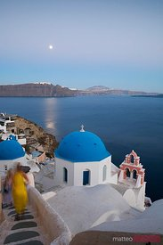 Supermoon over famous village of Oia with blue domed church, Santorini, Greece