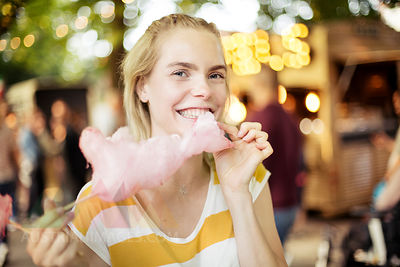 Portrait of young woman eating pink candy floss on streetfood festival