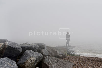 An atmospheric image of the shadowy figure of a man, standing on rocks by the ocean, on a misty morning.