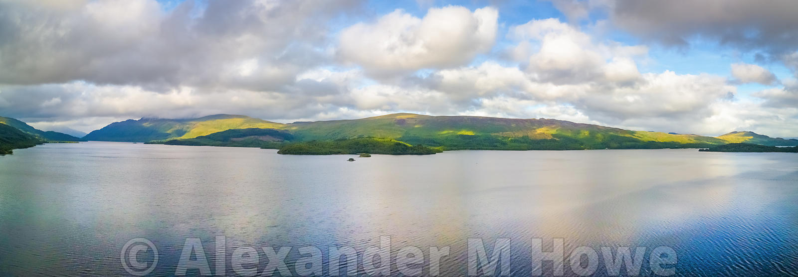 Looking across Loch Lomond towards Conic Hill with fluffy white clouds in the sky and patches of yellow sunlight on the hillsides.