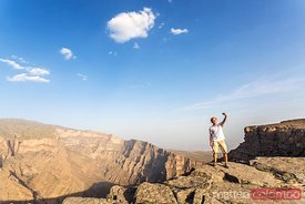 Man taking a selfie on the edge of canyon, Jebel Shams, Oman