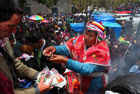 A yatiri or shaman blesses miniatures with coloured alcohol in scallop shells, Alasitas festival, La Paz, Bolivia