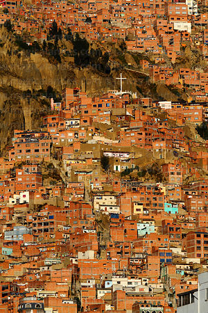 Cross on hilltop and brick houses on hillside in suburb of La Paz, Bolivia