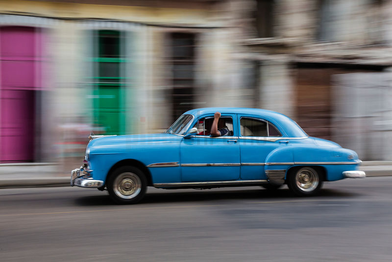 Vintage American Car Driving Past Colorful Doors in Central Havana