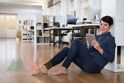 Woman sitting on floor in office using tablet