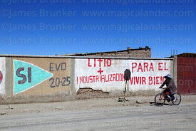 Woman cycling past propaganda showing support for Evo Morales and the industrialisation of the Salar de Uyuni's lithium reserves, Colchani, Bolivia