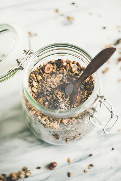 Buckwheat and chocolate granola with hazelnuts in glass jar, close-up
