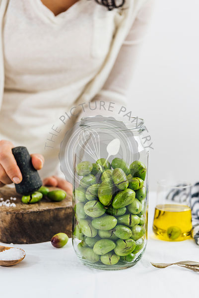 A woman cracking olives for brining. A glass jar full of green olives, a glass cup of olive oil and a wooden mallet on the table accompany.