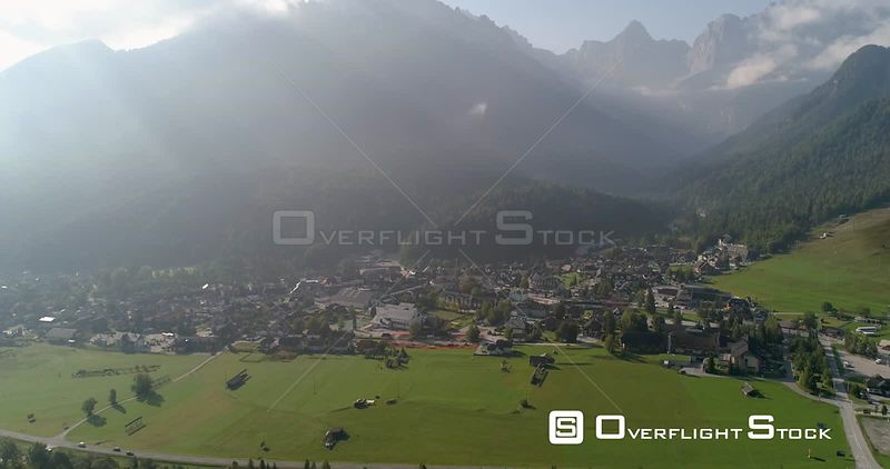 Alpine town, C4K aerial drone view away from the Kranjska Gora town and Trigolov national park, on a sunny summer day, in the Julian alps, Slovenia