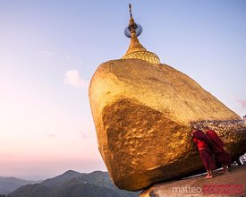 Two buddhist monks praying at the Golden rock, Myanmar