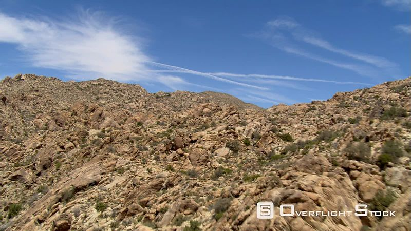 Close flight over rocky hills to wide view of desert landscape