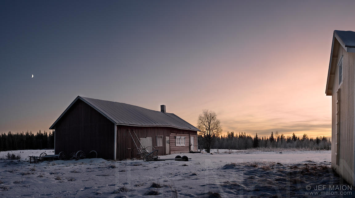 Abandoned barn and house in winter landscape