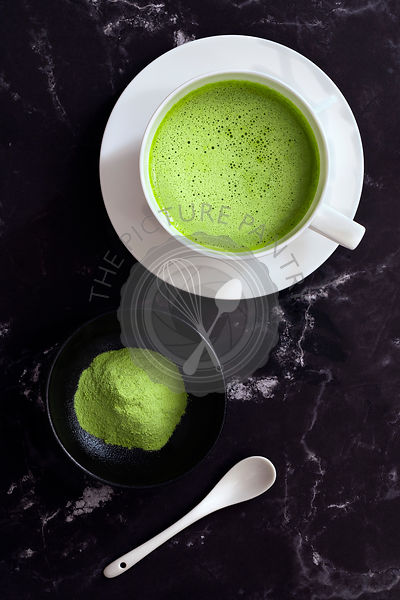 A cup of Matcha green tea with a small of bowl of Matcha tea powder and a spoon.