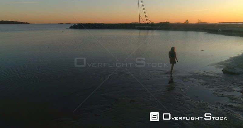 Girl walking at the sea, aerial view following a woman calming her feet in the sea, enjoying a warm summer sunset, on a sunny evening dusk, in Hanko, Uusimaa, Finland