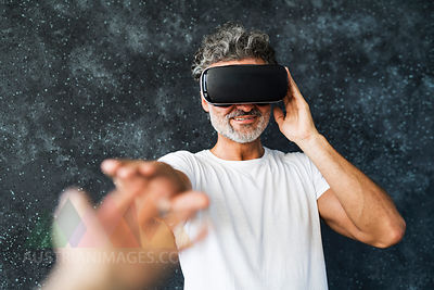 Mature man wearing VR glasses reaching out with hands