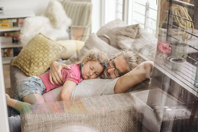 Father relaxing with daughter on sofa