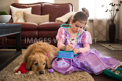 Female child plays veterinarian with dog
