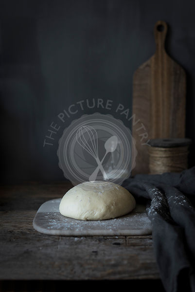 Bread dough proofing on a rustick kitchen table