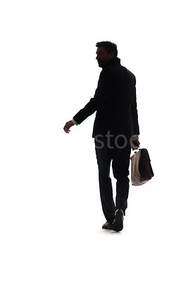A silhouette of a mystery man in a suit, walking and looking over his shoulder – shot from mid level.