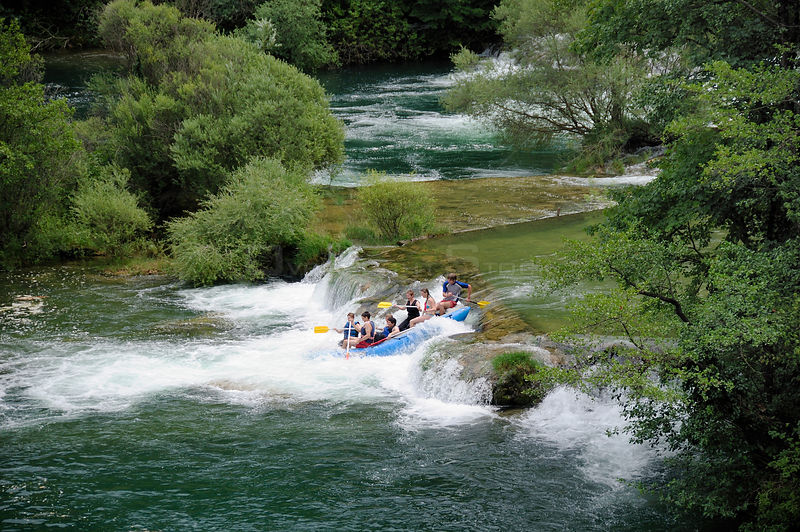 Tourists descending a waterfall on the Mreznica river in an inflatable white water raft, Zvecaj, Karlovacka, Croatia, July.