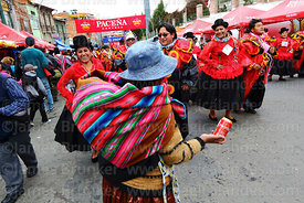 A street seller selling cans of beer to  dancers during parades for the Entierro del Pepino, La Paz, Bolivia