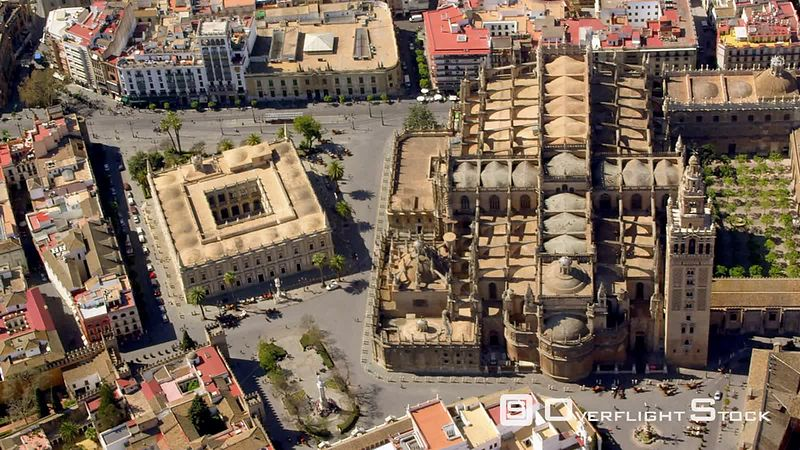 CIRCLING AERIAL VIEW OF SEVILLE CATHEDRAL WITH LA GIRALDA BELFRY AND THE ARCHIVOS DE LAS INDIAS THE GENERAL ARCHIVE OF THE INDIES THE SQUARE BUILDING TO THE LEFT OF THE CATHEDRAL) SPAIN