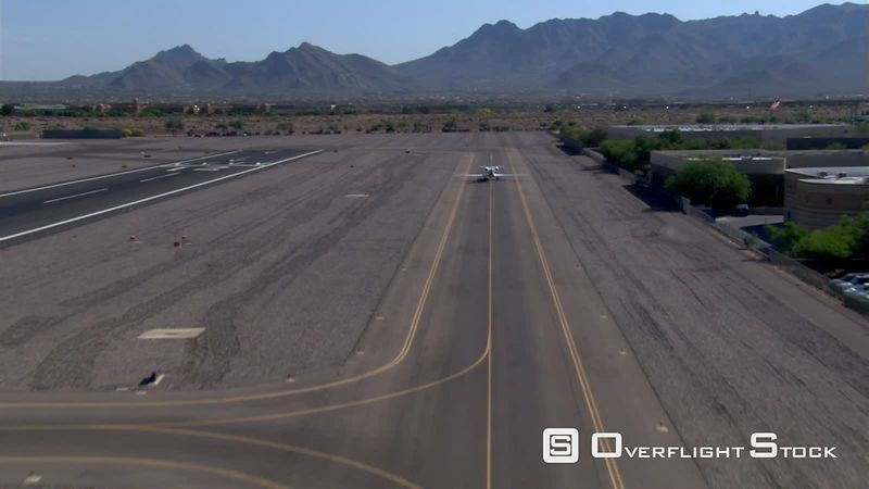 Aerial view of executive jet taxiing down runway