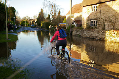 Flooding in Picturesque Streets in Kidlington Oxfordshire, Cyclist Rides Through Flooed Streets in Kidlington Oxfordshire