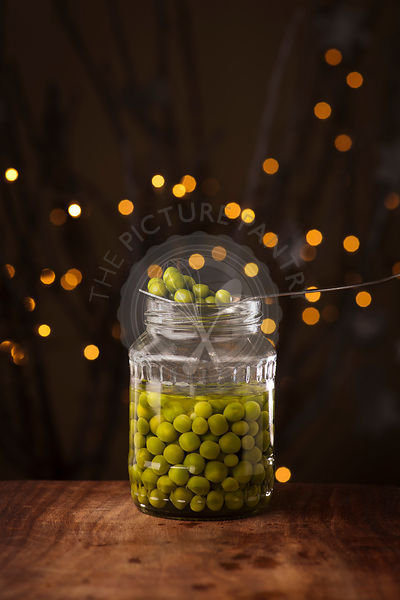 Open Glass jar of preserved peas on the dark background