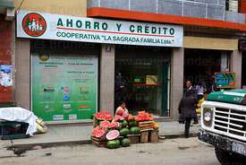 Aymara woman selling water melons in front of La Sagrada Familia cooperative bank , La Paz , Bolivia
