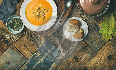 Fall warming pumpkin cream soup with croutons and seeds on board over rustic wooden background, copy space, flat-lay, top view