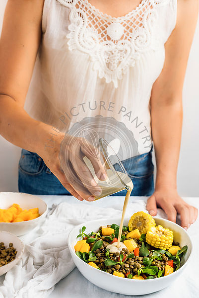A woman with a white summer top and jeans poring tahini dressing over a refreshing lentil salad photographed from front view.