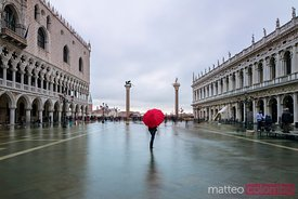 Woman with umbrella in St Marks square flooded, Venice