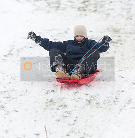 Boy sledging on Burrough Hills, Leicestershire