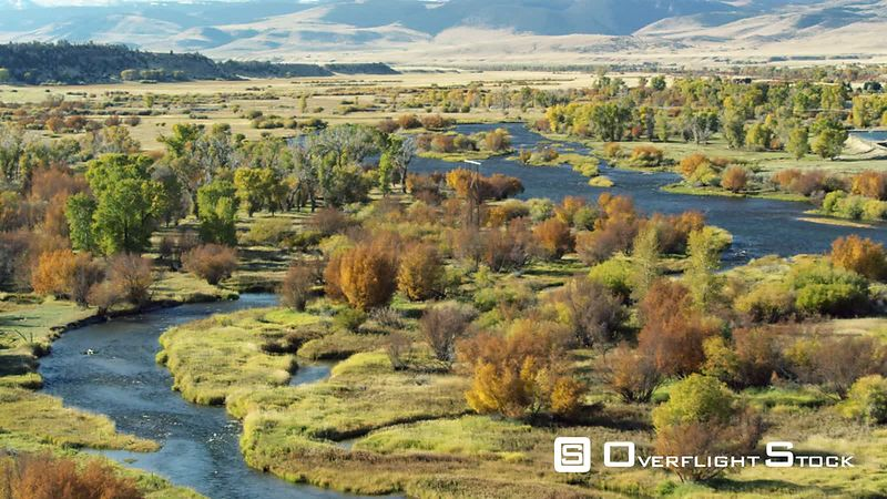 The Madison river winds through the bright autumn colors of changing Cottonwood, scrub oak and grasses in the Madison Valley, southwestern Montana, as the Gravelly mountain range towers in the distance