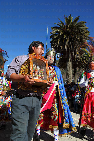 Festival patron carrying figure of Virgen del Carmen leading his Kapac Chunchu dance troupe , Paucartambo , Peru