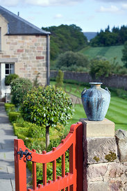 Bronze urn on gatepost and Topiary Walk leading to kitchen door.
