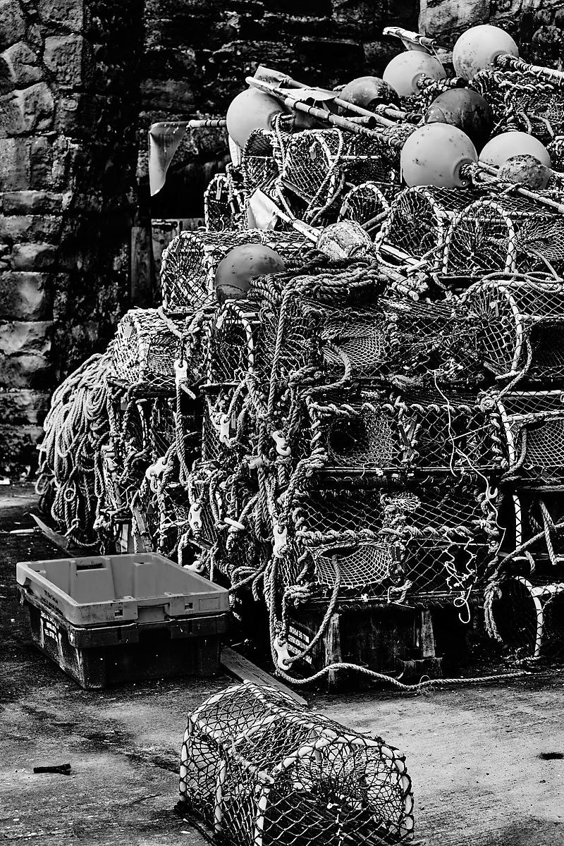 Lobster pots stacked against a stone wall in black and white