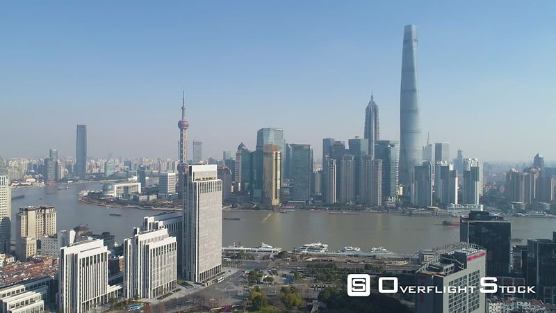 Shanghai Skyline at Sunny Day. Lujiazui Business District and Huangpu River. Blue Clear Sky. China. Aerial View. Drone is Flying Backward and Upward. Establishing Shot.